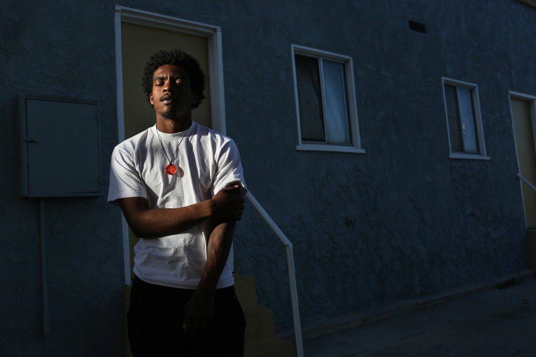 Ja'quest Jones, 19, stands for a portrait across the street from the apartment where he sometimes stays with his mom