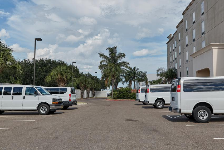 A series of white vans parked outside of the Hampton Inn hotel in McAllen. July 22, 2020.