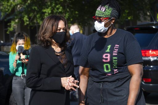 Democratic vice presidential candidate Sen. Kamala Harris, D-Calif., left, speaks with a supporter at the Busy Bee cafe during a campaign event, Friday, Oct. 23, 2020, in Atlanta.