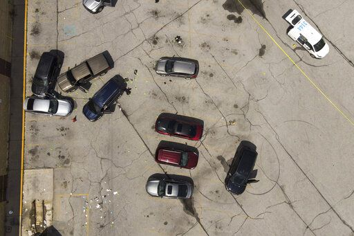 Officials inspect an area in the parking lot of a mall where two officers on the US Marshals' task force were allegedly shot in Baltimore, according to officials, Tuesday, July 13, 2021. The Marshal's wounds aren't thought to be life threatening.