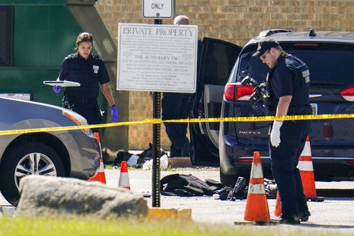 Body armor is seen near a minivan as a forensics worker inspects an area where two officers on the U.S. Marshals' task force were allegedly shot in Baltimore, according to officials, Tuesday, July 13, 2021. The Marshal's wounds aren't thought to be life-threatening.