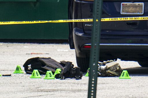 Body armor and evidence markers rest on the tarmac by a minivan near a mall parking area where two Baltimore city police officers were shot and a suspect was killed as a U.S. Marshals' task force served a warrant, Tuesday, July 13, 2021, in Baltimore, Md. The police officers were taken to the University of Maryland Medical Center with injuries that aren't thought to be life-threatening, county police spokeswoman Joy Stewart said.