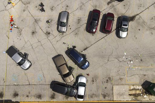 Officials inspect an area in the parking lot of a mall where two officers on the US Marshals' task force were allegedly shot in Baltimore, Tuesday, July 13, 2021.