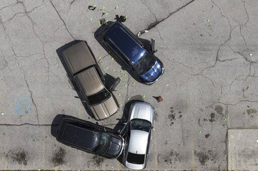Officials inspect an area in the parking lot of a mall where two officers on the U.S. Marshals' task force were shot in Baltimore, according to officials, Tuesday, July 13, 2021. The Marshal's wounds aren't thought to be life-threatening.