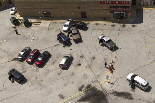 Officials inspect an area in the parking lot of a mall where two officers on the US Marshals' task force were allegedly shot in Baltimore, Tuesday, July 13, 2021. The Marshal's wounds aren't thought to be life threatening.